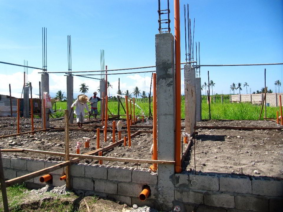 Photo showing columns, wirings, and plumbing at ongoing construction